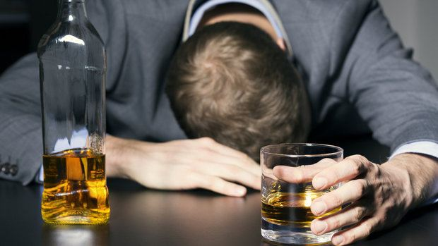 alcohol addiction - drunk businessman holding a glass of whiskey on the table